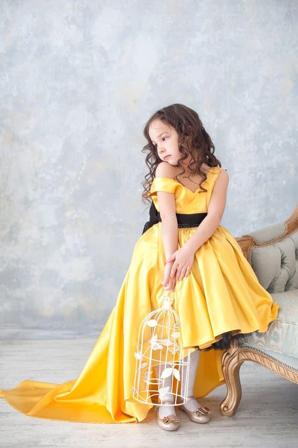 Stående av att le lilla flickan i guld- klänning för prinsessa med fjärilar fotografering för bildbyråer