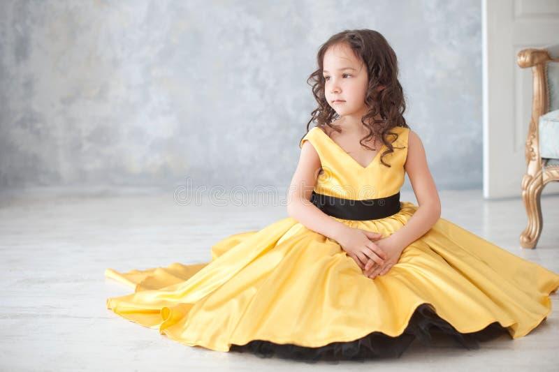 Stående av att le lilla flickan i guld- klänning för prinsessa med fjärilar arkivfoton