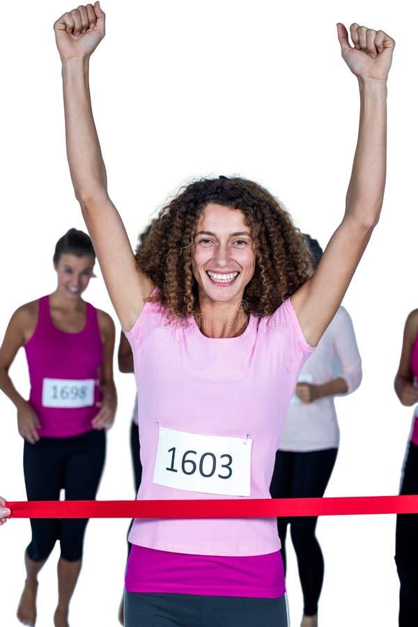 Stående av att le mållinje för kvinnlig idrottsman nen för vinnare korsningen med lyftta armar royaltyfri bild