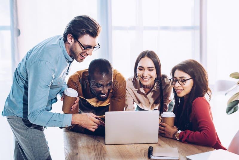 stående av att le mångkulturellt affärsfolk som tillsammans arbetar på bärbara datorn royaltyfri foto