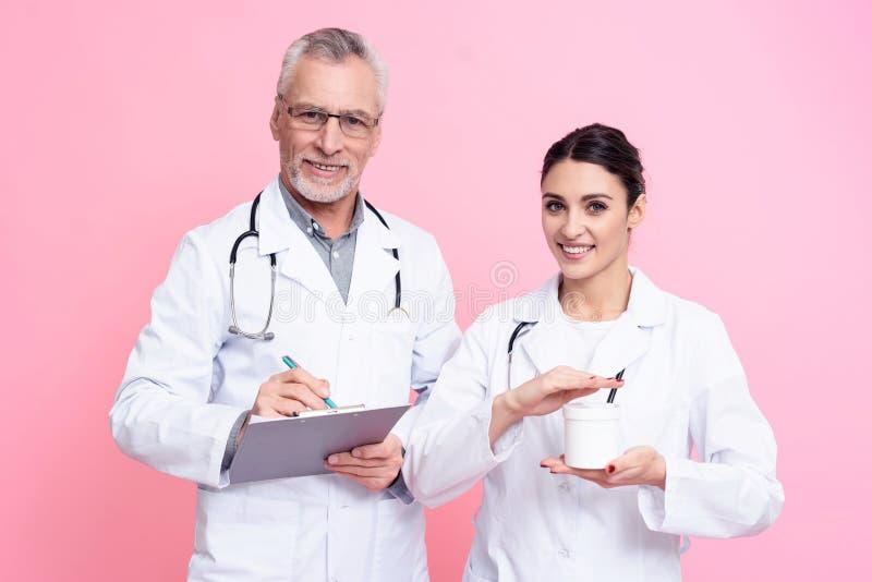Stående av att le man- och kvinnligdoktorer med stetoskop som rymmer den isolerade skrivplattan och vita asken royaltyfria foton