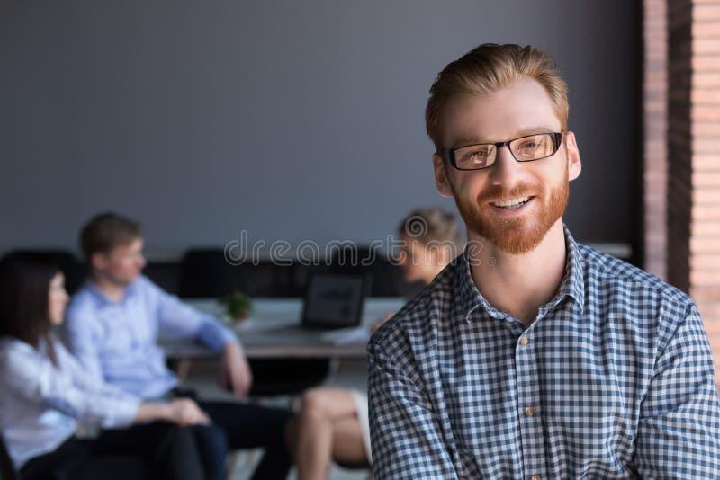 Stående av att le manlig anställd som poserar under företagsförhandsmöte royaltyfria foton