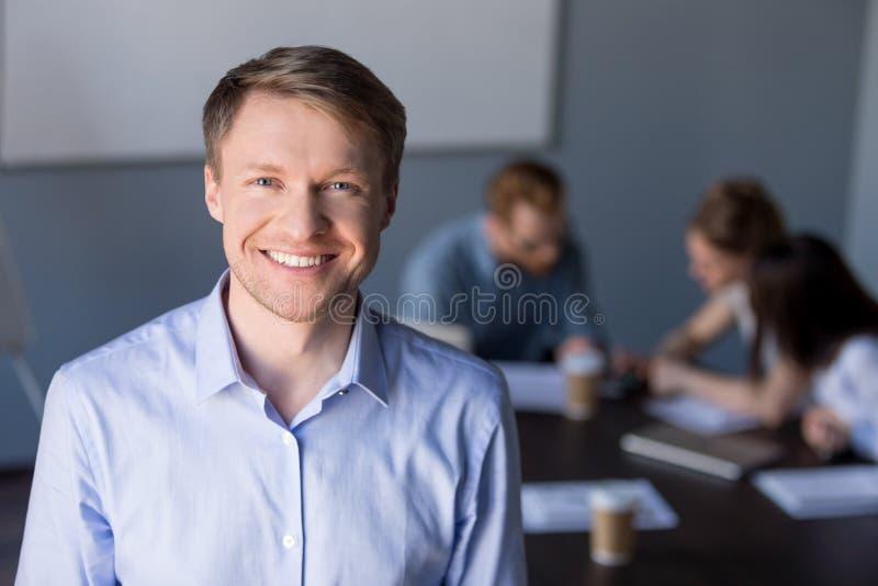 Stående av att le manlig anställd som poserar under förhandsmöte arkivfoton
