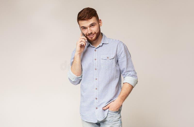 Stående av att le mannen som talar på telefonen på studiobakgrund arkivfoto