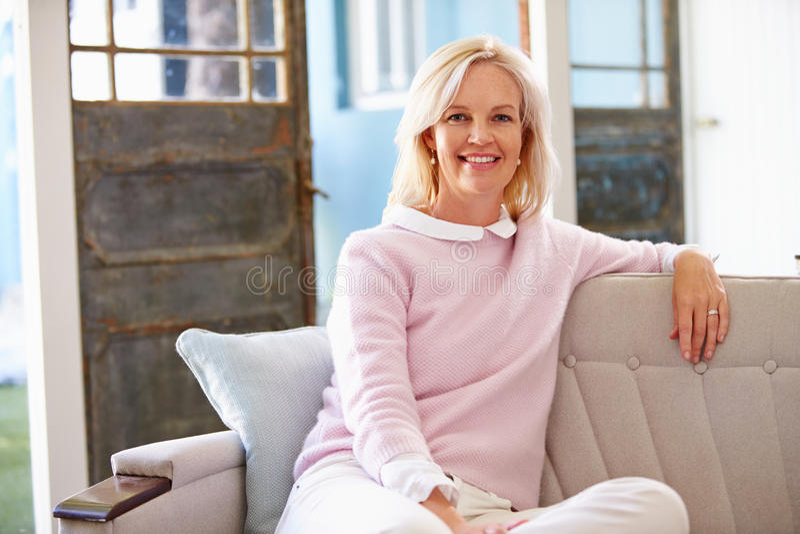Stående av att le moget kvinnasammanträde på Sofa At Home royaltyfria foton