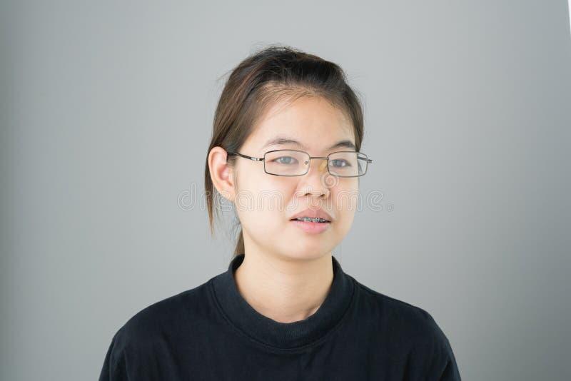 Stående av att le pålagda asiatiska unga kvinnor hänglsen på grå färg ger en bakgrund ett mjukt ljus fotografering för bildbyråer