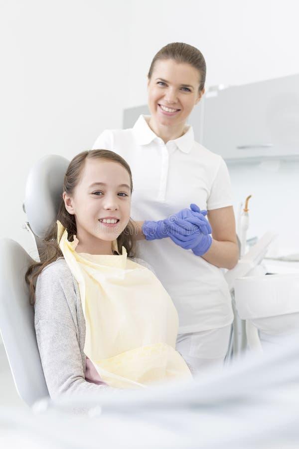 Stående av att le patienten och tandläkaren på den tand- kliniken royaltyfri bild
