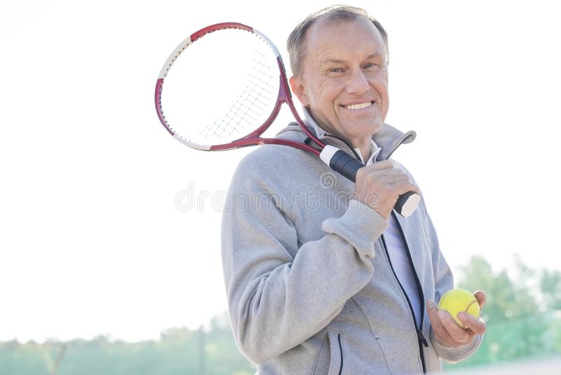Stående av att le pensionerat anseende för hög man med tennisracket och bollen mot klar himmel på solig dag fotografering för bildbyråer