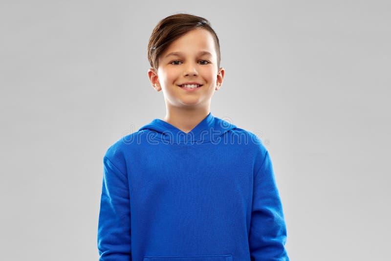 Stående av att le pojken i blå hoodie fotografering för bildbyråer