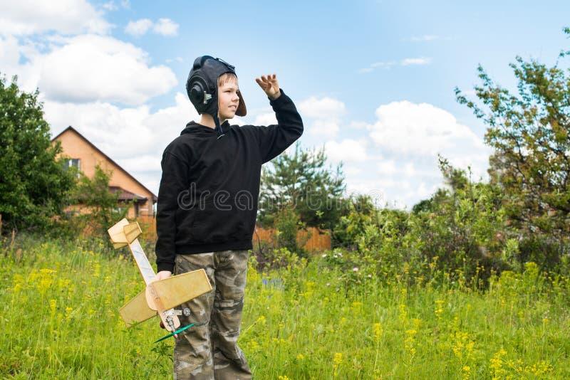 Stående av att le pojken i pilot- hjälm med den plana modellen på himmel royaltyfri foto