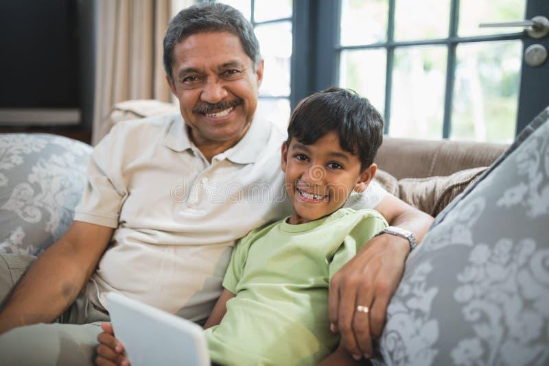 Stående av att le pojken med farfadern som rymmer den digitala minnestavlan, medan sitta hemma royaltyfri foto