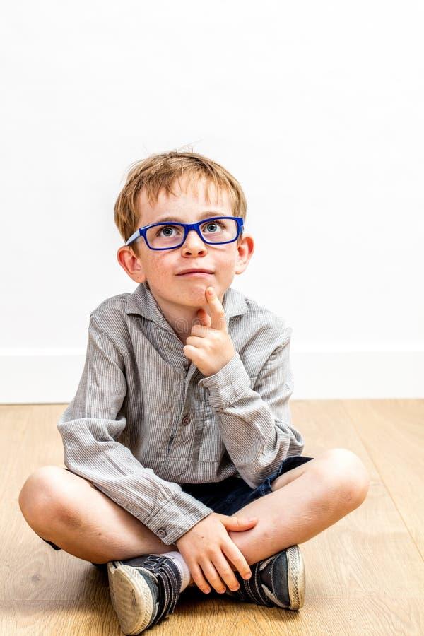 Stående av att le pojken med glasögon som tänker för barnharmlöshet arkivbild