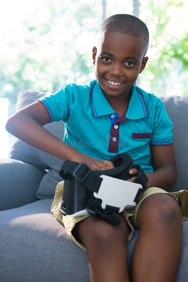 Stående av att le pojken som hemma justerar virtuell verklighethörlurar med mikrofon arkivbild