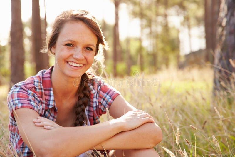Stående av att le sammanträde för ung kvinna i bygd arkivfoto