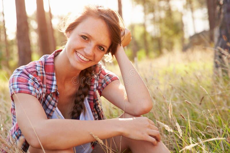 Stående av att le sammanträde för ung kvinna i bygd royaltyfri bild