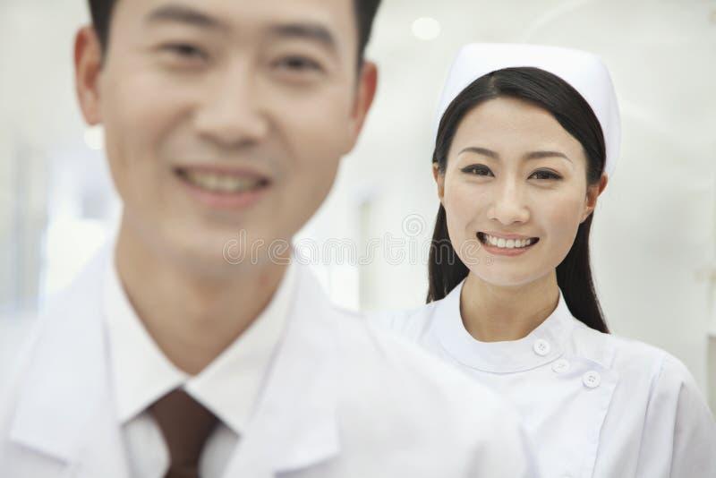 Stående av att le sjuksköterskan, doktor i förgrund, i sjukhus arkivbild
