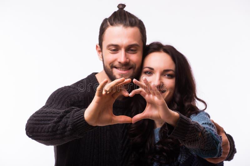 Stående av att le skönhetflickan och hennes stiliga pojkvändanandeform av hjärta vid deras händer royaltyfri bild