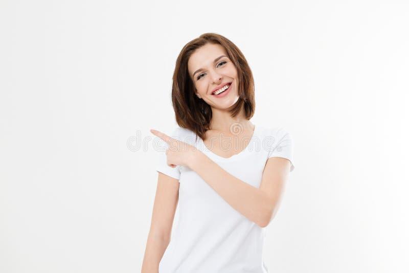 Stående av att le skjortan för sommar t för ung caucasian kvinna som den bärande pekar på kopieringsutrymme vid fingret som isole fotografering för bildbyråer