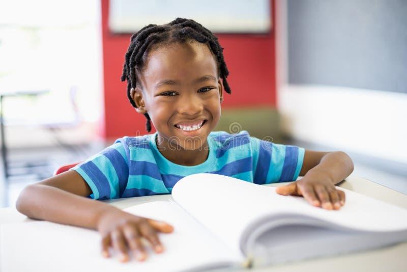 Stående av att le skolpojkeläseboken i klassrum arkivbild