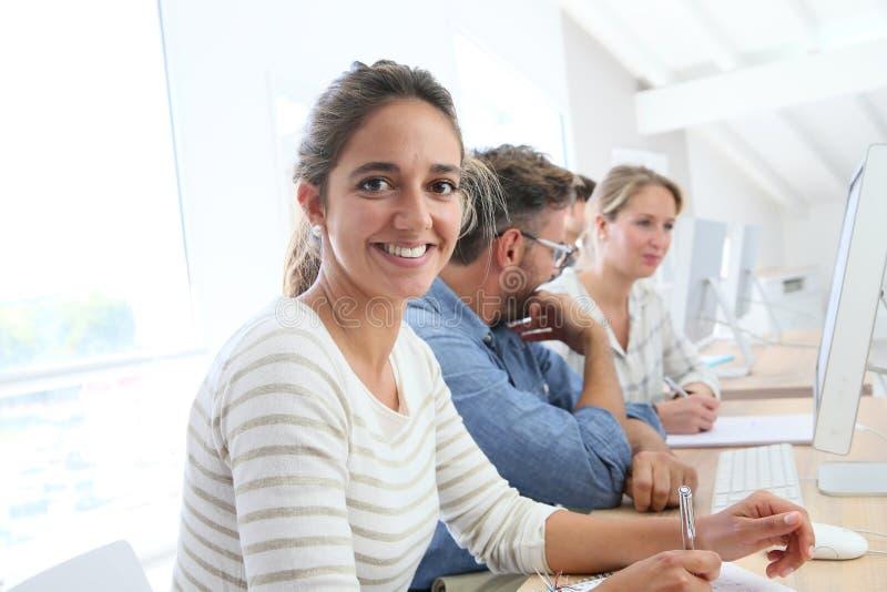 Stående av att le studenten med klasskompisar och läraren arkivbild