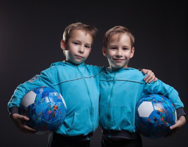 Stående av att le tvilling- pojkar som poserar med bollar royaltyfri fotografi