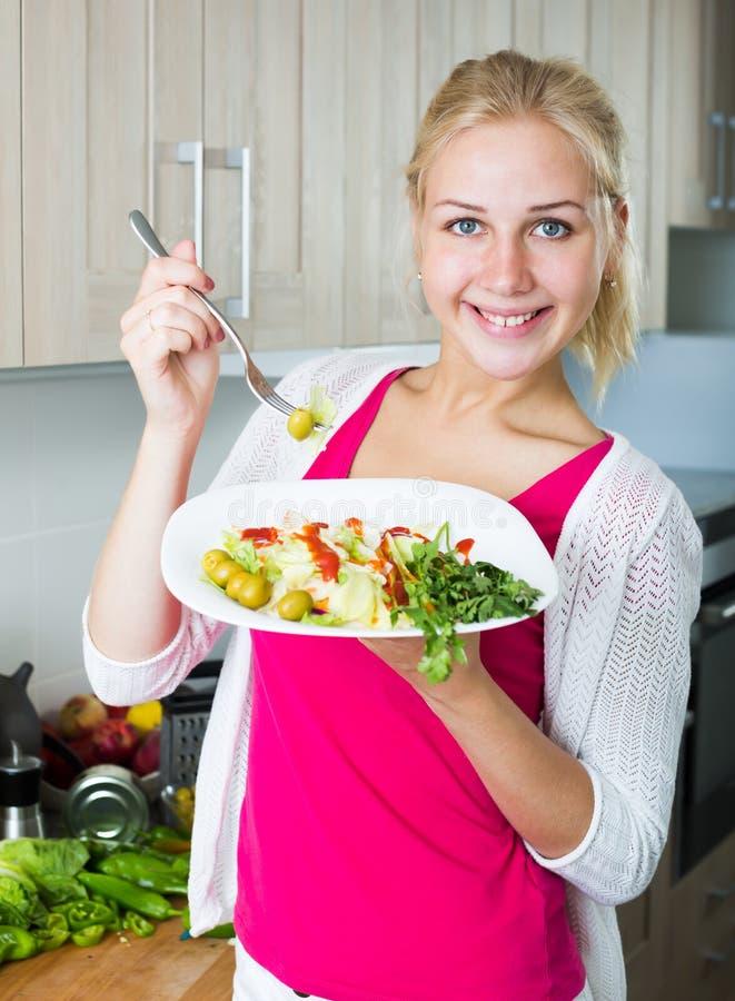 Stående av att skratta den blonda flickan som äter sallad fotografering för bildbyråer
