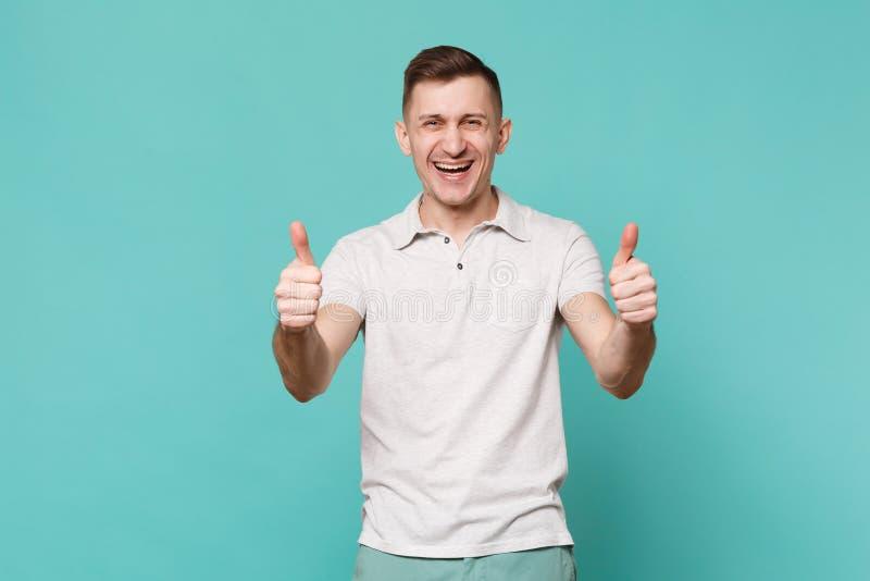 Stående av att skratta den lyckliga unga mannen i tillfällig kläder som står som visar tummar som isoleras upp på den blåa turkos arkivbild