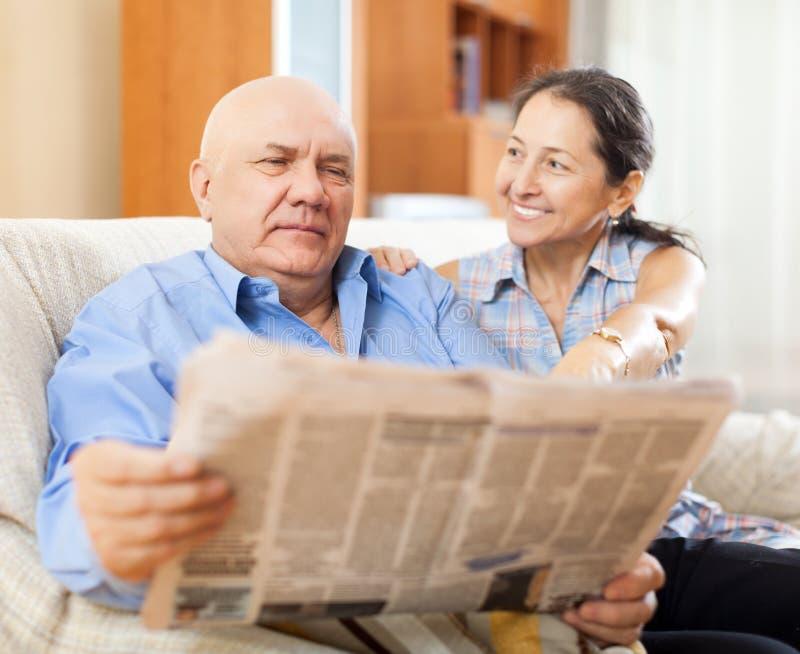 Stående av att skratta den mogna kvinnan och åldringmannen med tidningen fotografering för bildbyråer