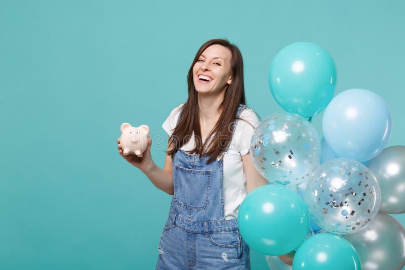 Stående av att skratta den unga kvinnan i grov bomullstvillkläder som rymmer den piggy pengarbanken som firar med färgrika luftba royaltyfri bild