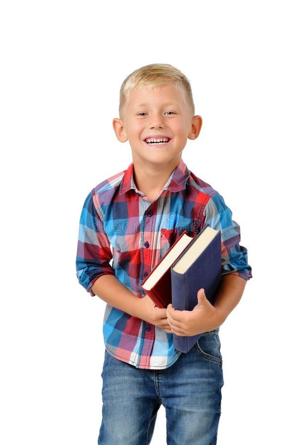 Stående av att skratta den unga pojken med böcker som isoleras på vit bakgrund Utbildning royaltyfri foto