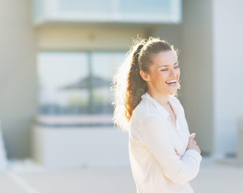 Stående av att skratta kvinnan som framme står av husbyggnad arkivfoton