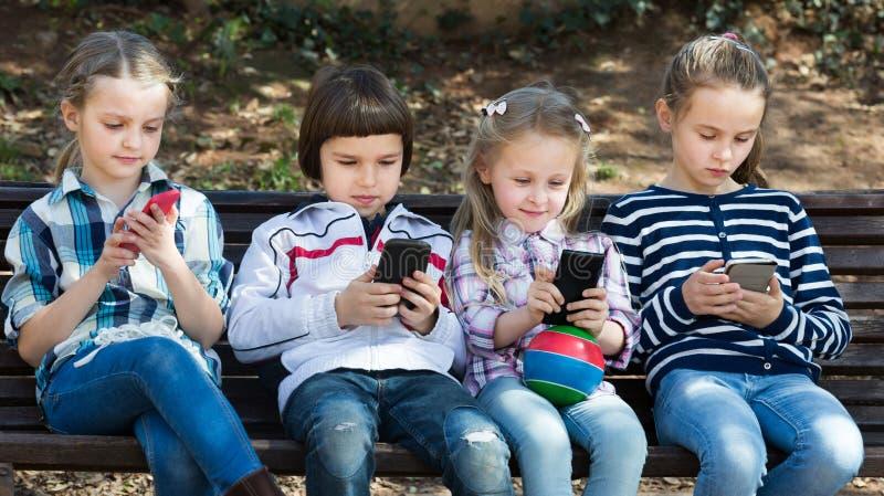 Stående av att skratta ungar som spelar med telefoner royaltyfri foto