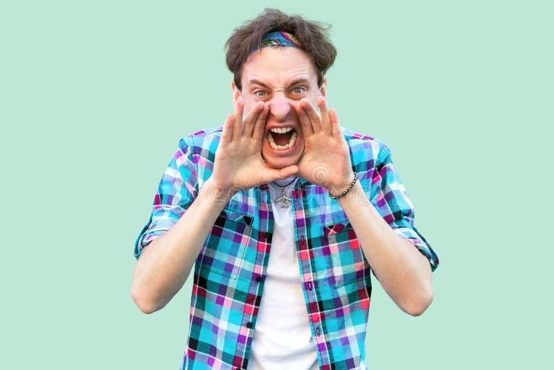 Stående av att skrika den unga mannen i tillfälligt blått rutigt skjorta- och huvudbindelanseende med händer på hans framsida som royaltyfria foton