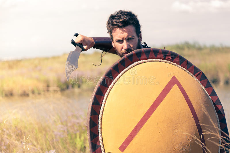 Stående av att slåss den forntida krigaren i harnesk med svärdet och skölden arkivbilder
