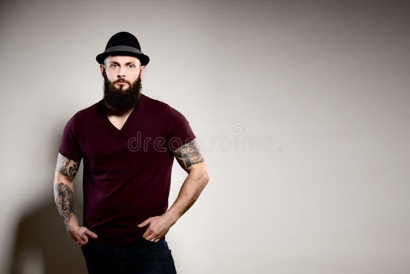 Stående av att stå den stiliga skäggiga mannen i hatt arkivbilder