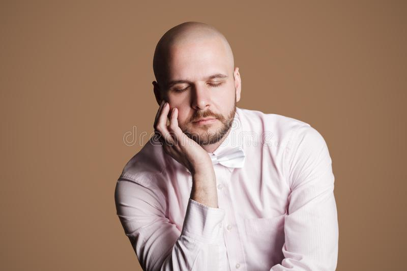 Stående av att tänka den stiliga skäggiga skalliga mannen i ljus - rosa shi arkivfoto