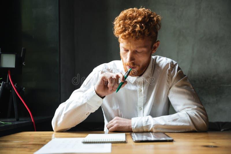 Stående av att tänka den unga readheadmannen i den vita skjortan som sitter royaltyfri foto