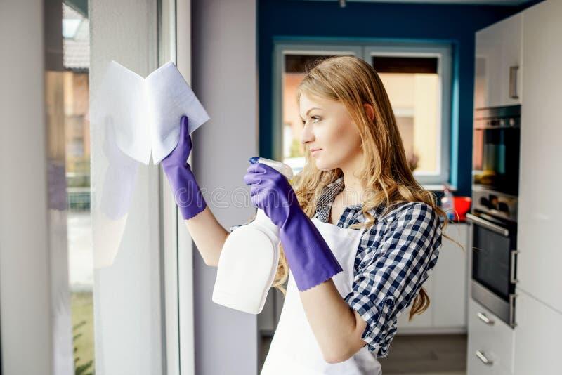 Stående av attraktiva lokalvårdfönster för ung kvinna i huset arkivbild