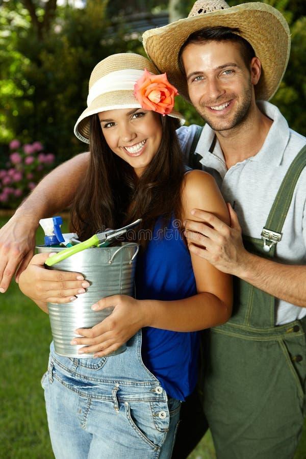 Stående av attraktiva unga arbeta i trädgården par royaltyfri fotografi