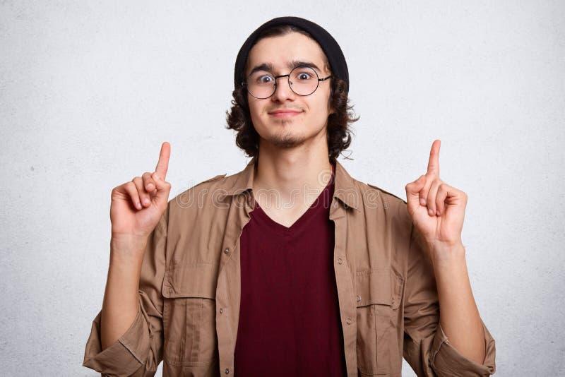 Stående av attraktivt bärande glasögon för ung man, skjorta, omslag och lock som pekar upp med hans fingrar som isoleras på vit arkivbild