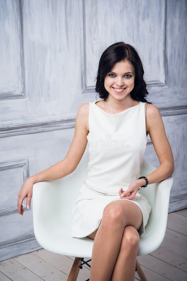 Stående av attraktivt sammanträde för ung kvinna i en stol Elegant vit klänning Vit golv och vitvägg i bakgrunden royaltyfria bilder