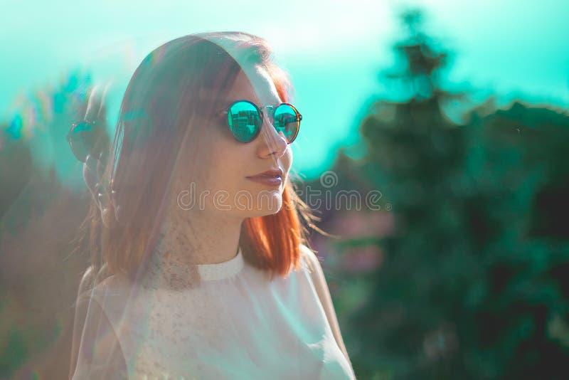 Stående av bärande exponeringsglas för härlig redhairkvinna royaltyfria foton