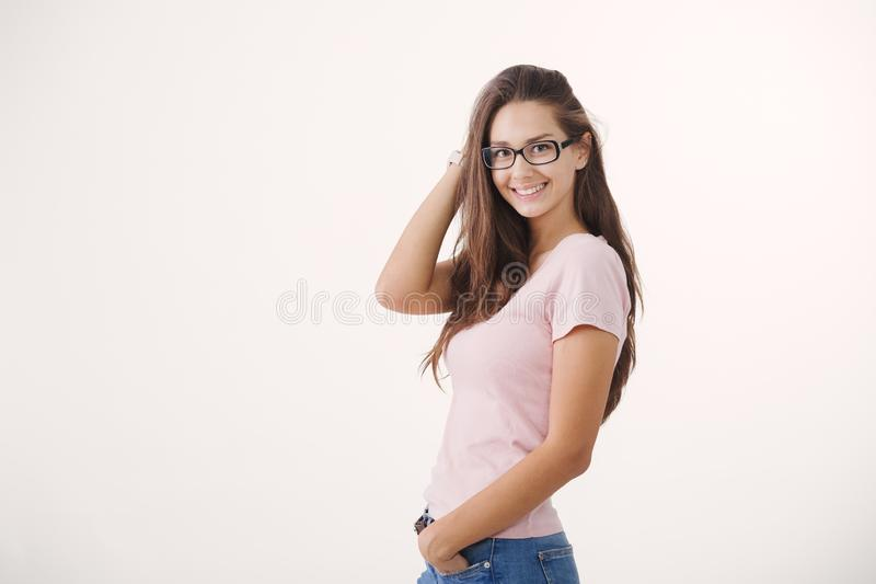 Stående av bärande exponeringsglas för ung gladlynt brunhårig kvinna mot vit bakgrund royaltyfri foto