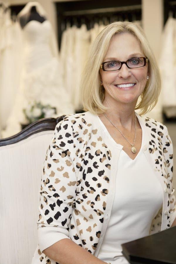 Stående av bärande glasögon för en lycklig hög kvinna som sitter i brud- boutique fotografering för bildbyråer
