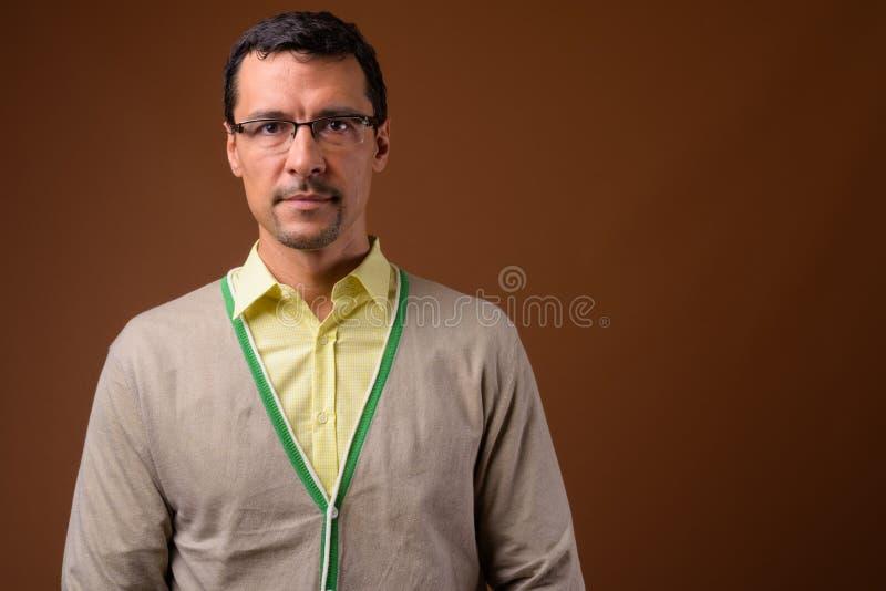 Stående av bärande glasögon för stilig man mot brun bakgrund arkivbild