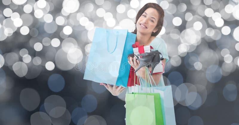 Stående av bärande shoppingpåsar för kvinna och höga häl mot bokeh royaltyfri foto