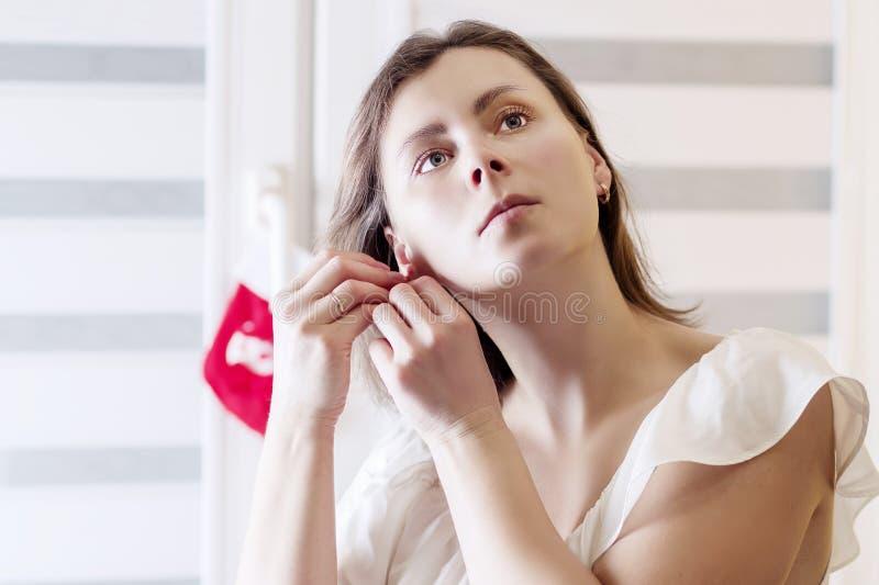 Stående av bärande smyckenörhängen för ung kvinna hemma royaltyfri foto
