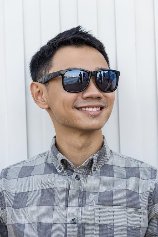 Stående av bärande solglasögon för en asiatisk stilig man i stad arkivbild