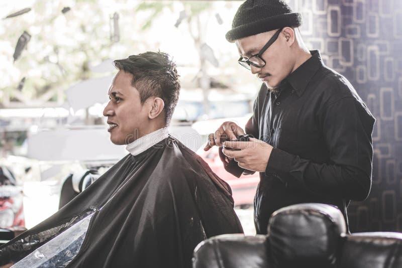 Stående av barberarefrisyren ett dräkthår med handen och pomada i frisersalong eller salong arkivbilder