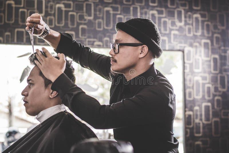 Stående av barberaren som gör hårsnittet av hans attraktiva man i frisersalong royaltyfria bilder